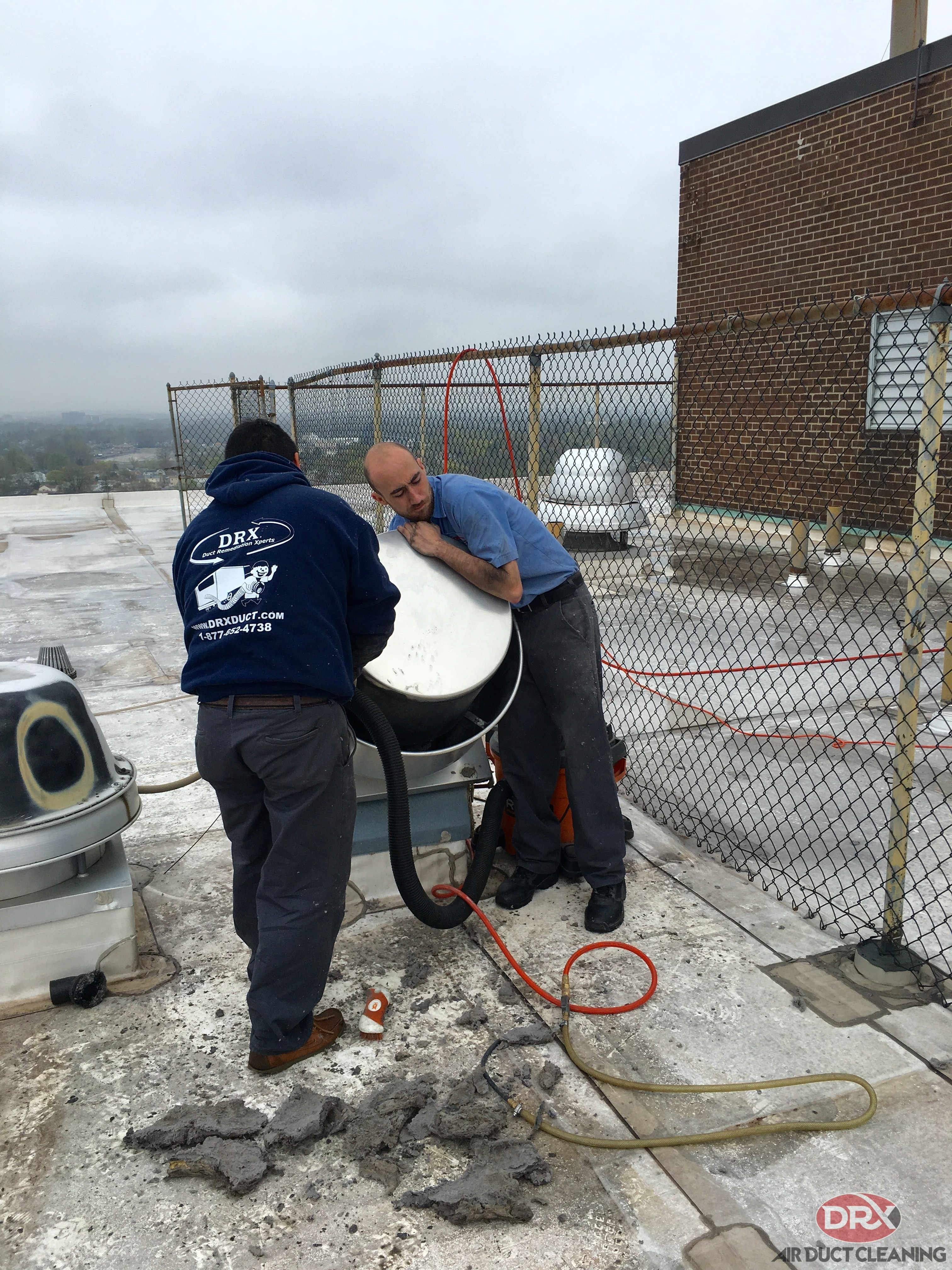 Two professionals working together to clean ductwork