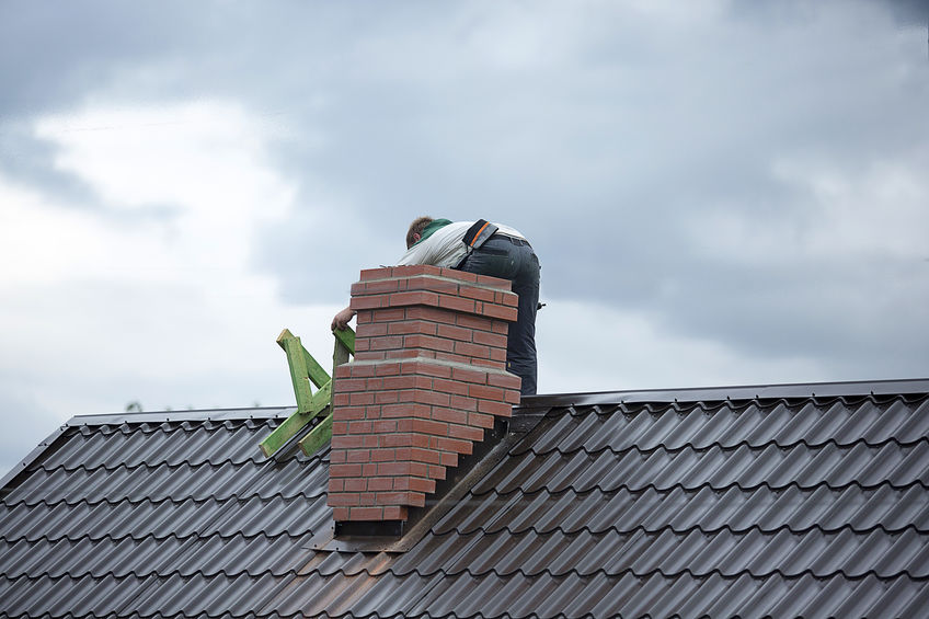 Worker on Roof Repairing Brick for Chimney Cleaning Services