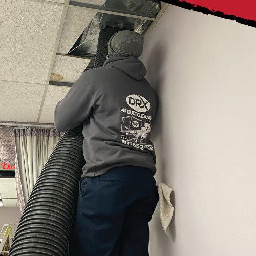 Technician cleans ductwork